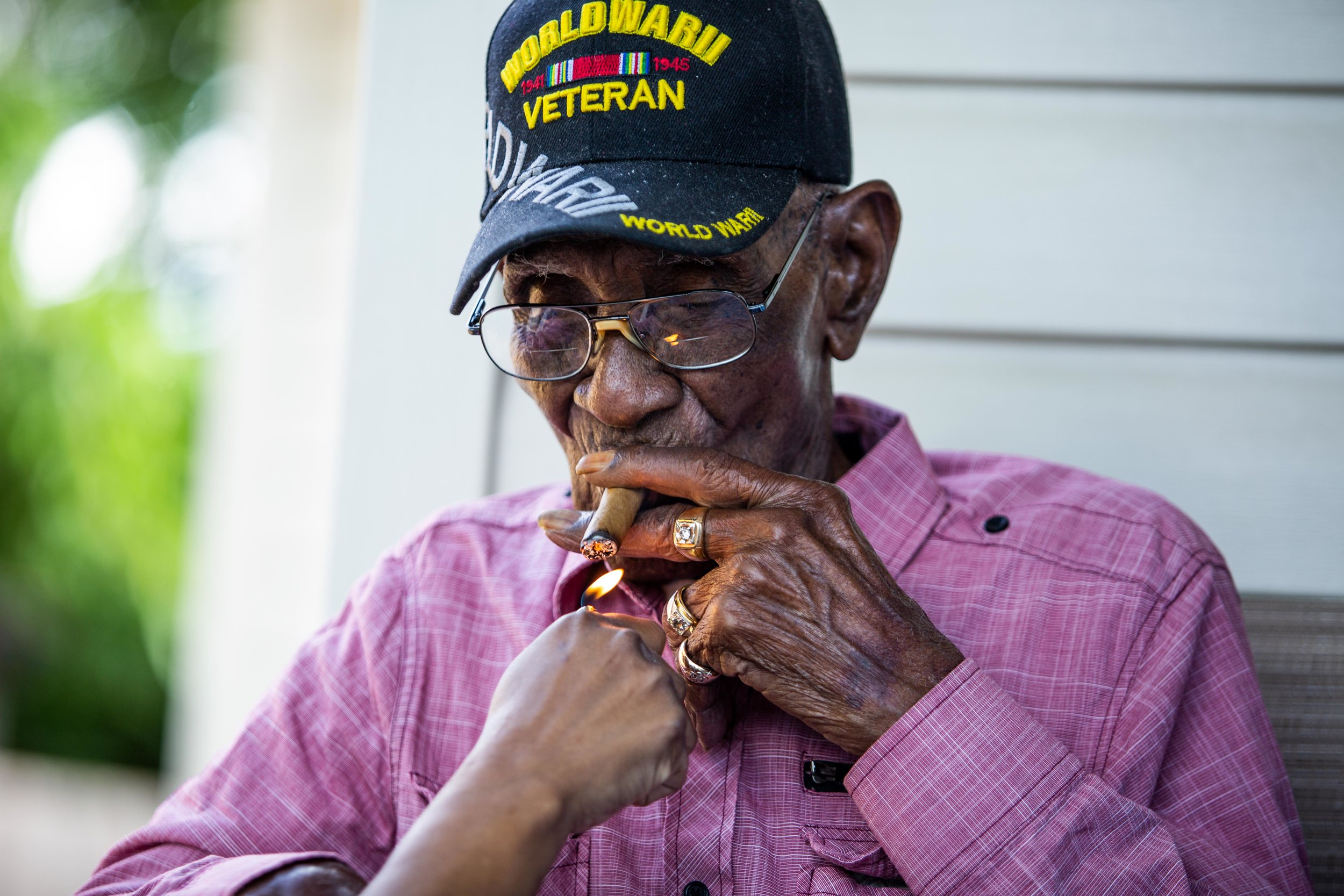 AUSTIN, TEXAS. May 11, 2018. Richard Overton, America's oldest living WWII veteran, lights a cigar on the front porch of his East Austin home during a public party celebrating his 112th birthday.Montinique Monroe for KUT News