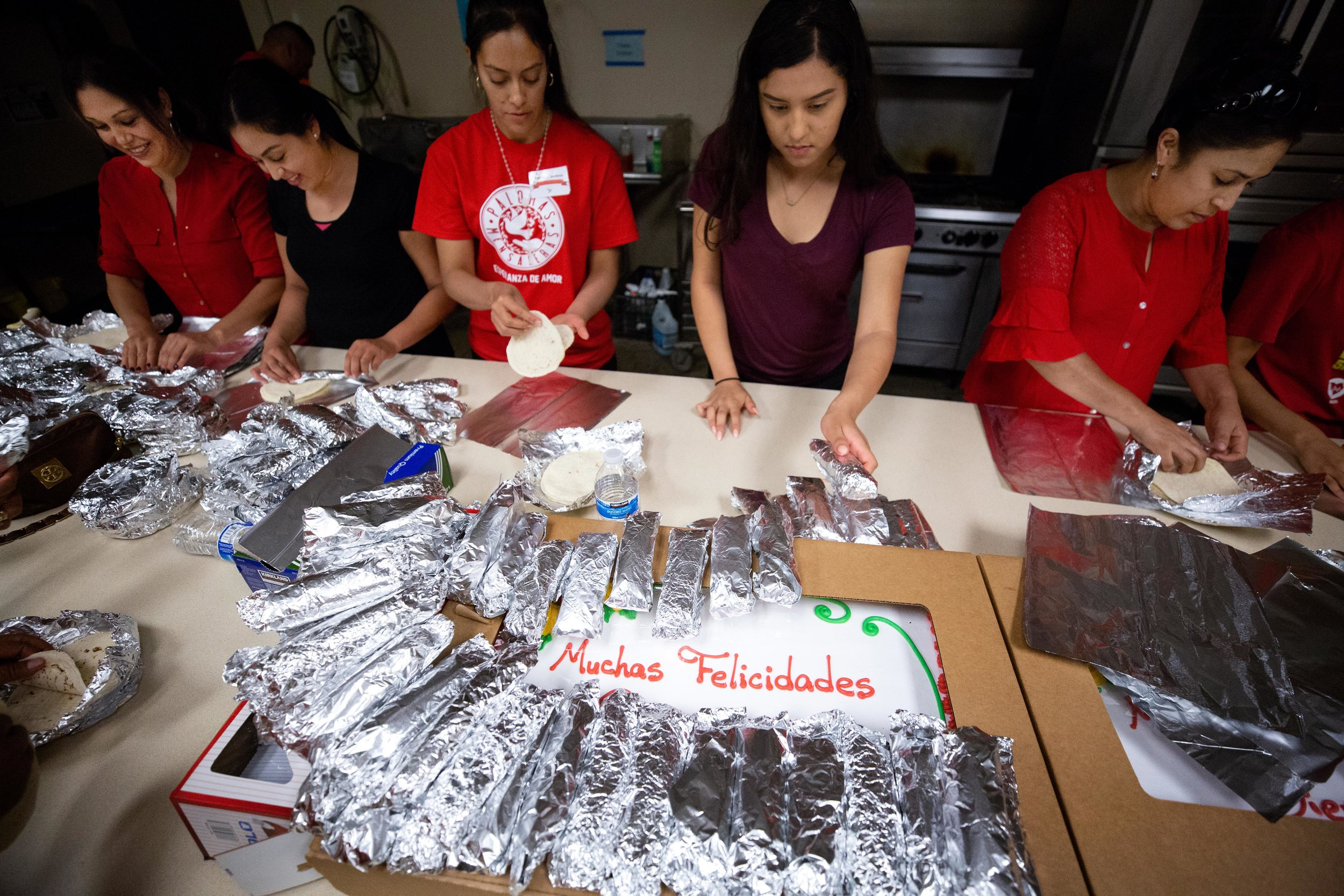 ROUND ROCK, TX. August 10, 2018. Volunteers Lizbeth Hernandez (middle), 14, and Monica Barriga (left) roll tortillas during a family reunification event. Palomas Mensajeras (homing pigeons) came to the Austin area to reunite families who've been separated for over a decade because of undocumented status. Montinique Monroe for KUT News