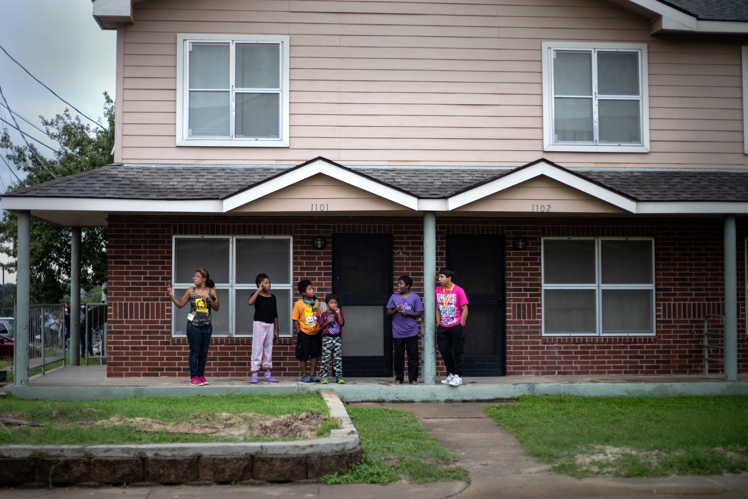 Tracie Moreno (left) and her children watch an Austin Police Department SWAT team response to Booker T. Washington Terrace apartments on Oct. 19, 2018.