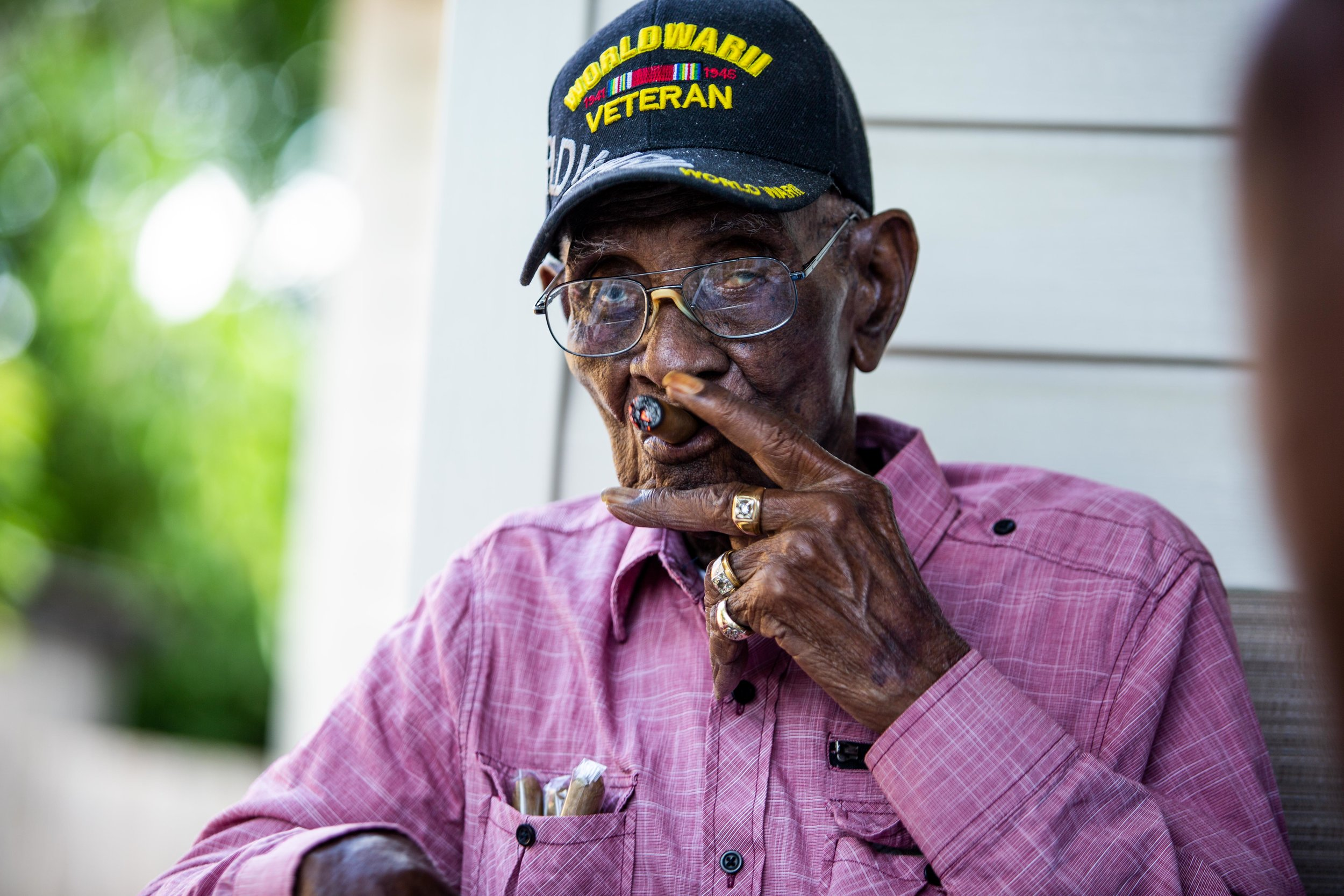 AUSTIN, TEXAS. May 11, 2018. Richard Overton, America's oldest living WWII veteran, smokes a cigar on the front porch of his East Austin home during a public party celebrating his 112th birthday. Montinique Monroe for KUT News