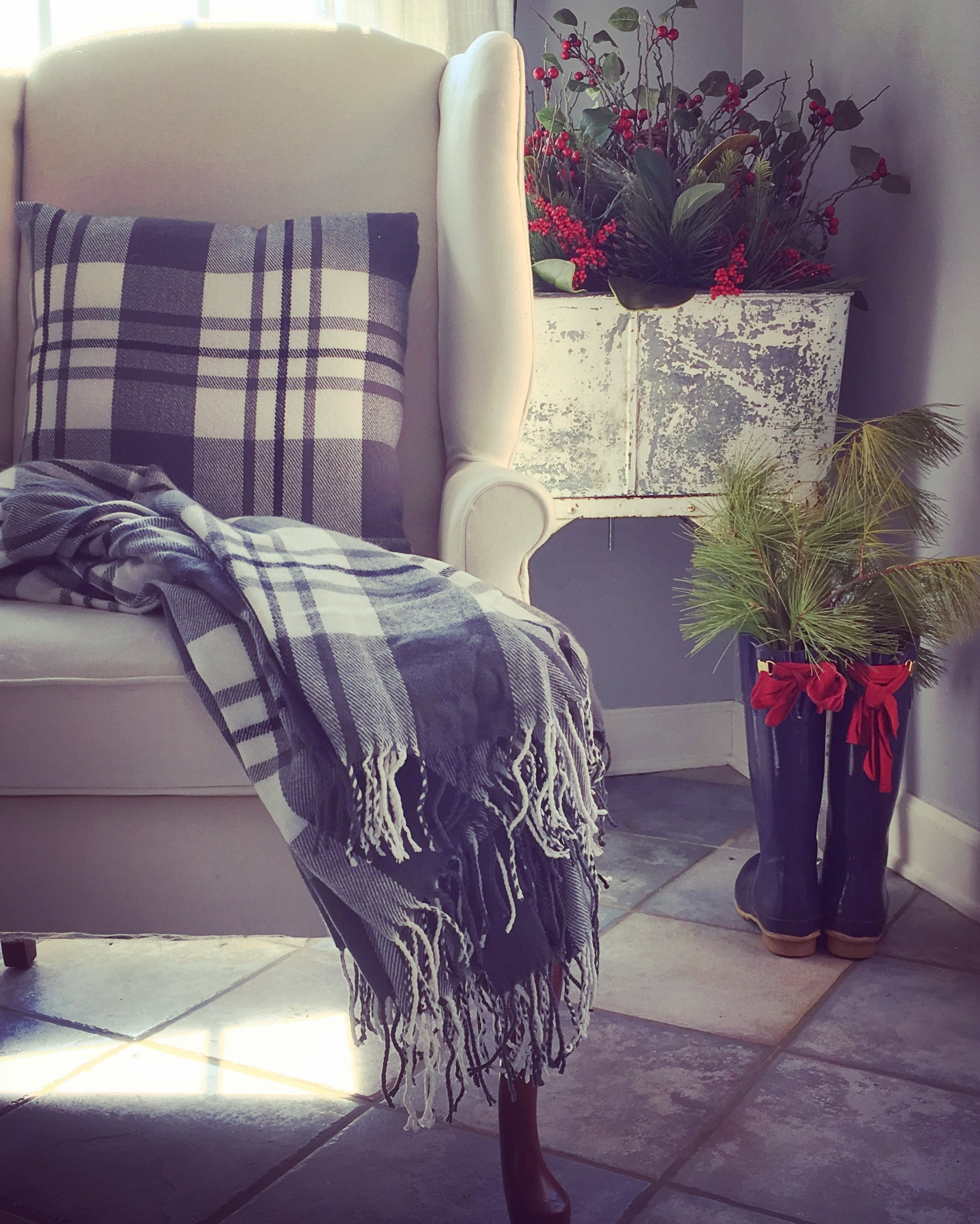Seasonal accent pillows and a throw blanket switched out on this neutral chair instantly warmed up my kitchen nook. We replaced our summer plant with some Christmas greenery, in our Voss tub by the back door. I love the antique patina on this piece my husband purchased for me when we were antiquing. I set my greenery in my boot temporarily as I was decorating and loved it enough to leave it :).