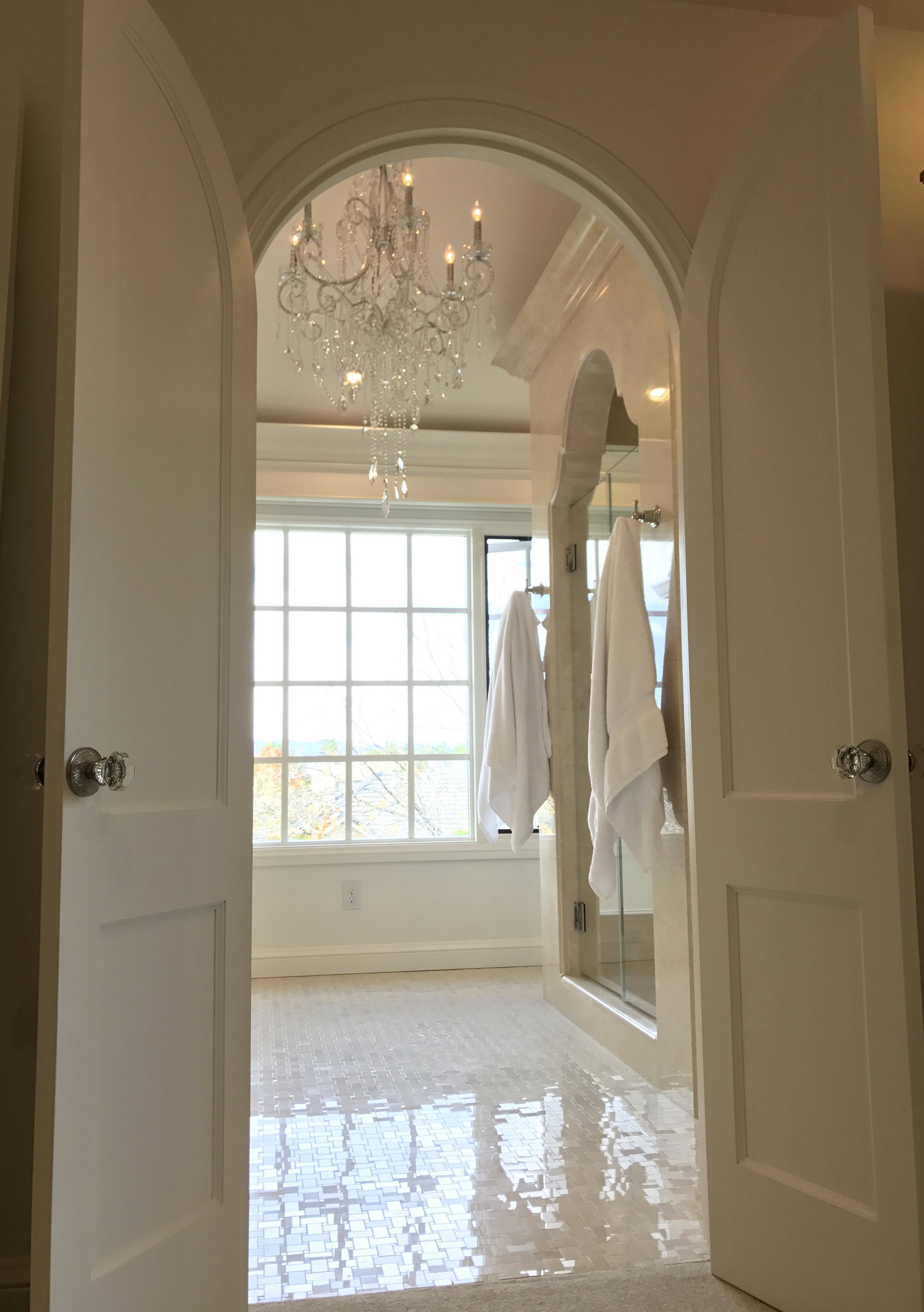 Double doors were installed between the master bedroom and bathroom for noise control and privacy.  The bathroom ceilings were raised  and two stunning Chandi chandeliers fill the space with light. The sparkling marble floor and chandeliers beckon you into this sanctuary.