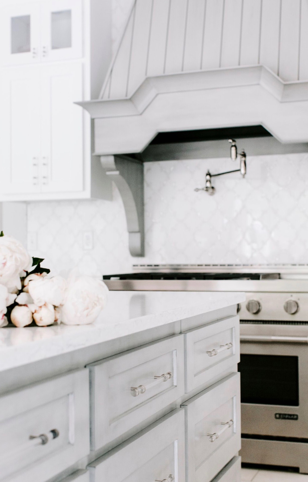 We chose a washed light grey for the island to offer a contrast and a sense of grounding to the space.  Hoods are the jewelry of the kitchen, and we chose to match the island with this hood.