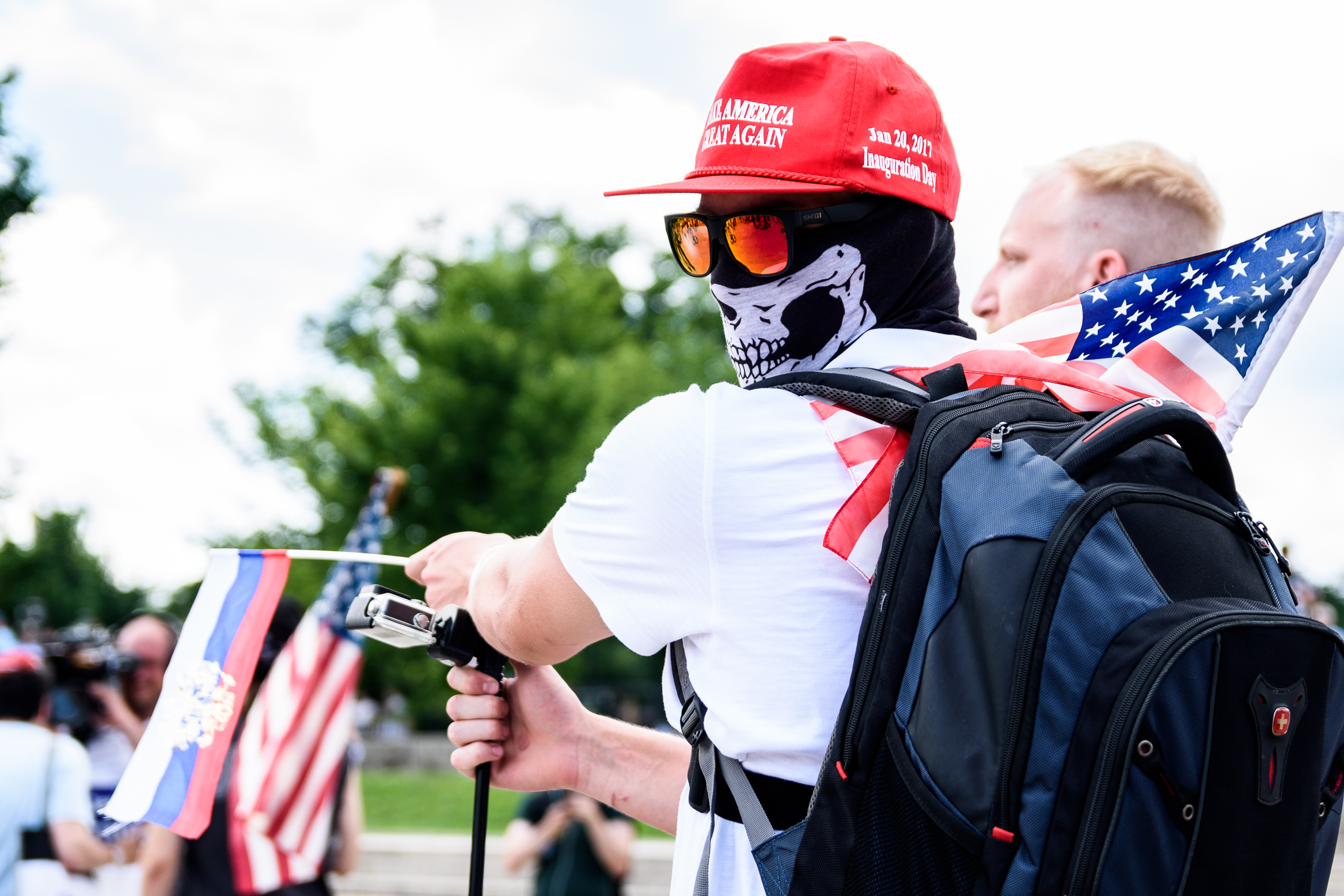 A masked Trump supporter waves Russian and American flags on the steps to the Lincoln Memorial.