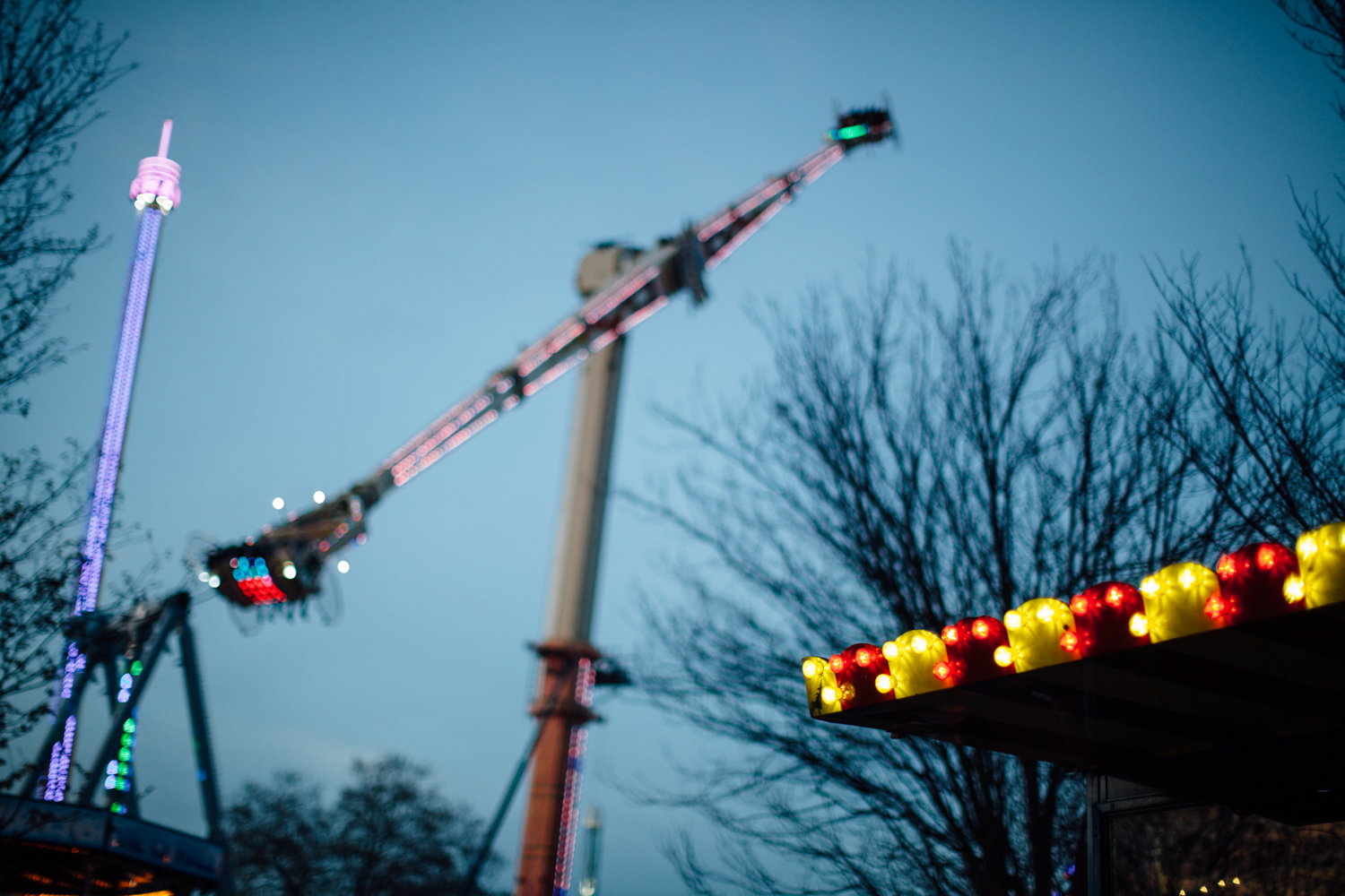 A food market stand's lights and attraction rides.