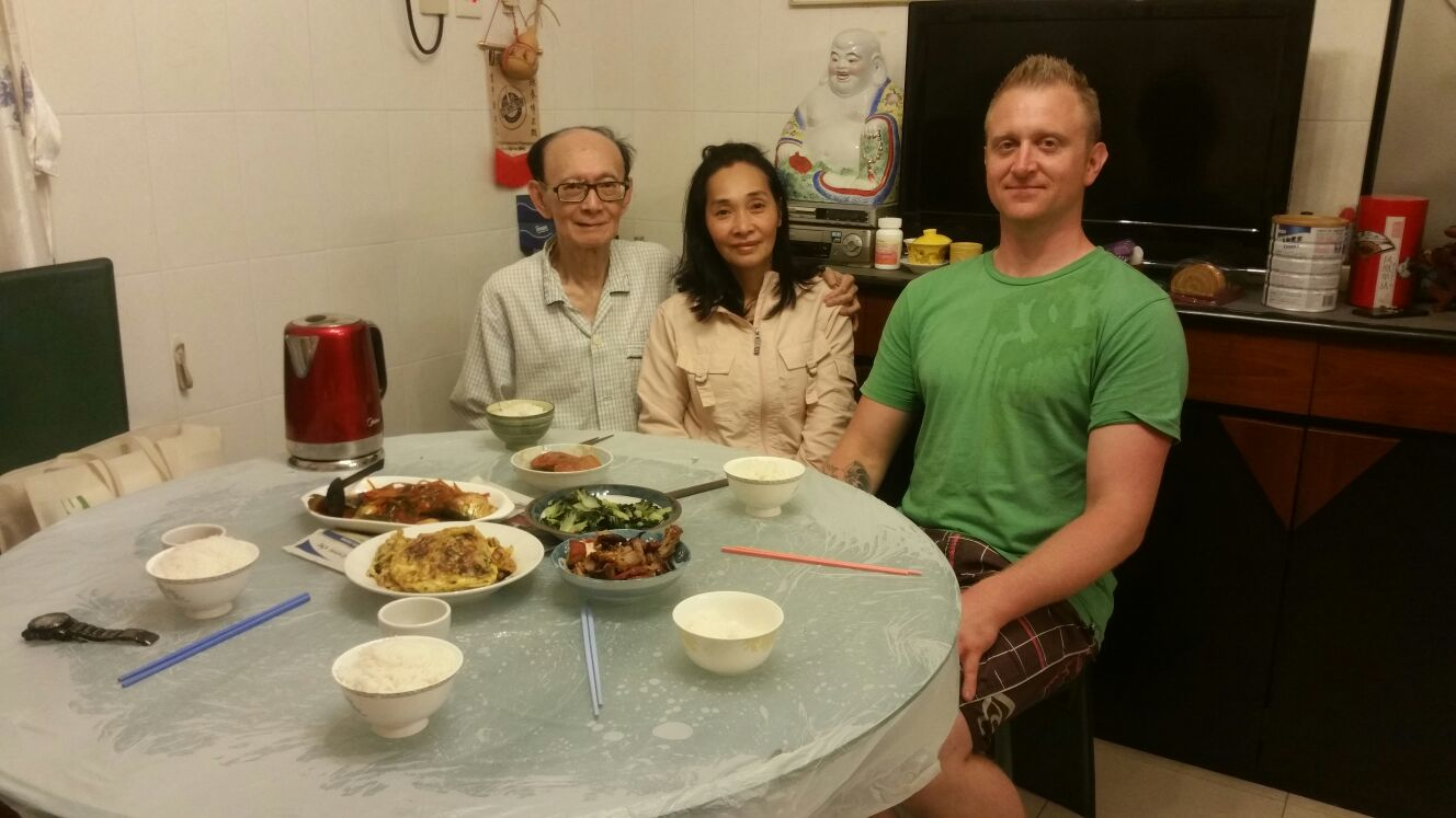 Robert Ley sitting for dinner with his Sifu and Simo in their home preparing to eat a wonderful meal
