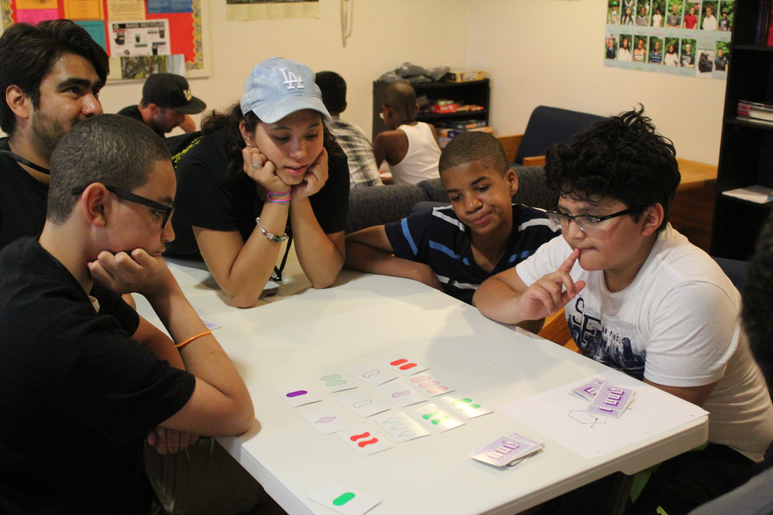 Pictured above: Counselor Kaylynn (middle) and instructor Javier (left of Kaylynn) play Set, a matching game which requires players to recognize patterns in a set of cards, with students Jack, Storm, and Seb.