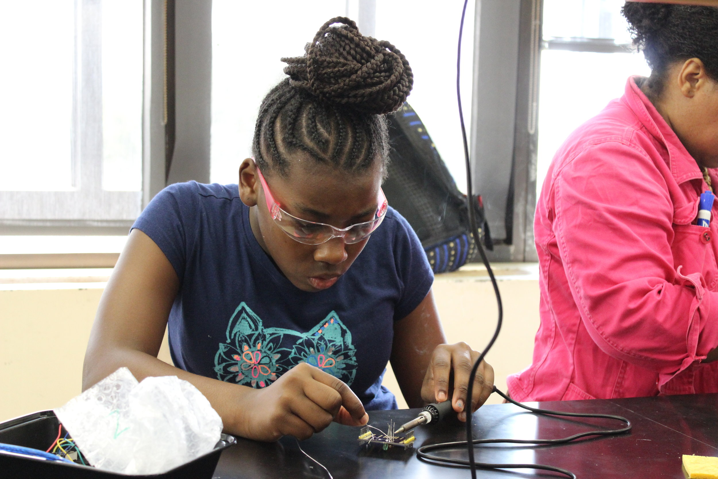 Zanahya, a rising 7th grader, learns to solder at BEAM 6 in 2018. Aisha, who learned to solder at BEAM 7 five years earlier was the teaching assistant for this course.