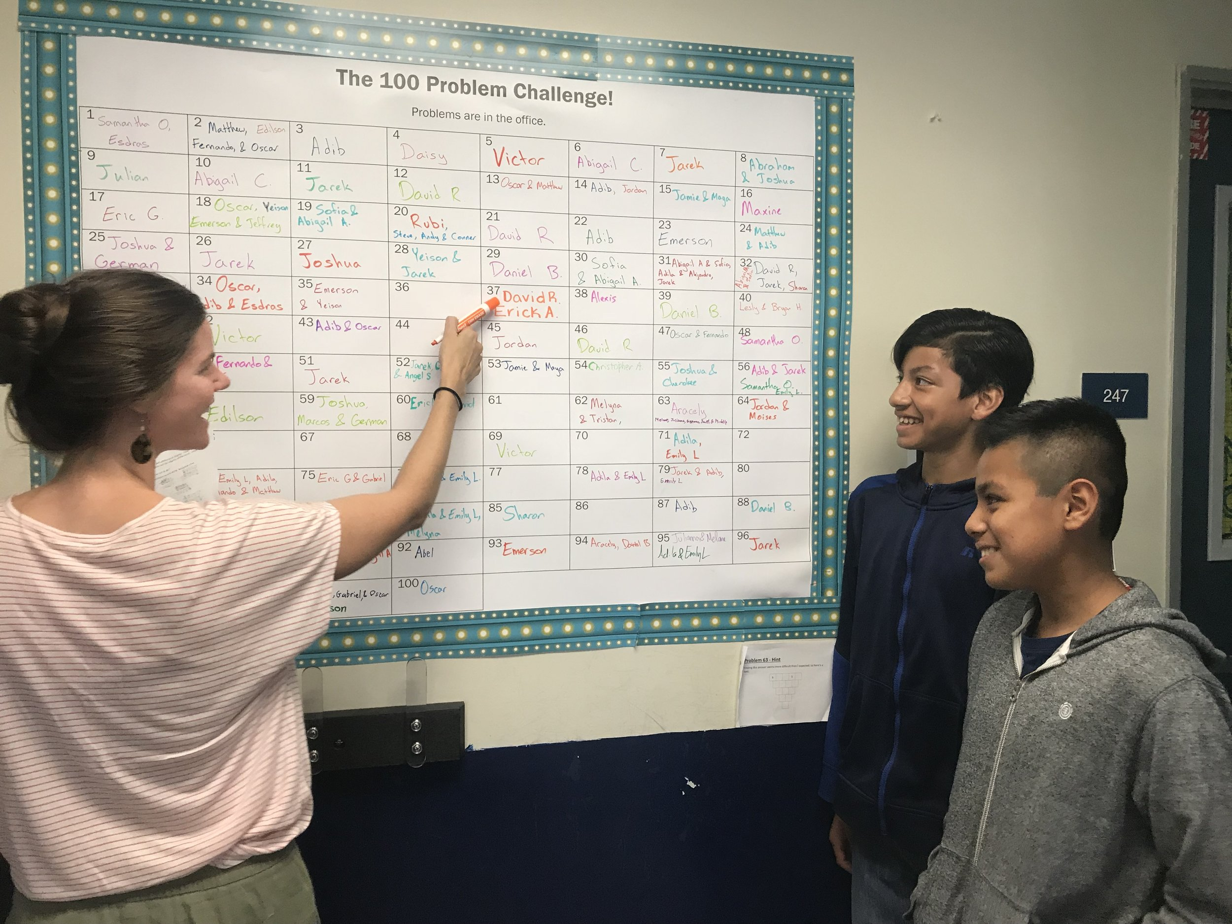 David (right) and Erick A. (middle) solved one of the challenge problems, so Meghan (left) writes their names on the poster.