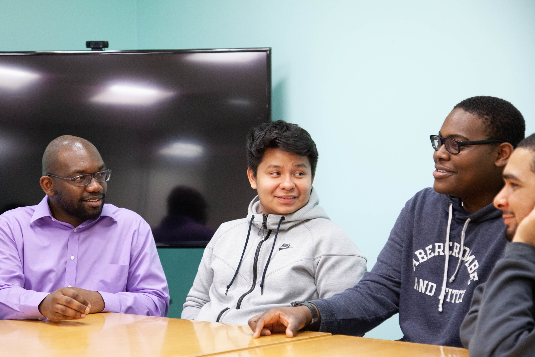 Ayinde works with Teo (BEAM '14), Jahleel (BEAM '15), and Zyan (BEAM '15) at the Young Men's Empowerment Group. Photo taken by Peter Dressel.
