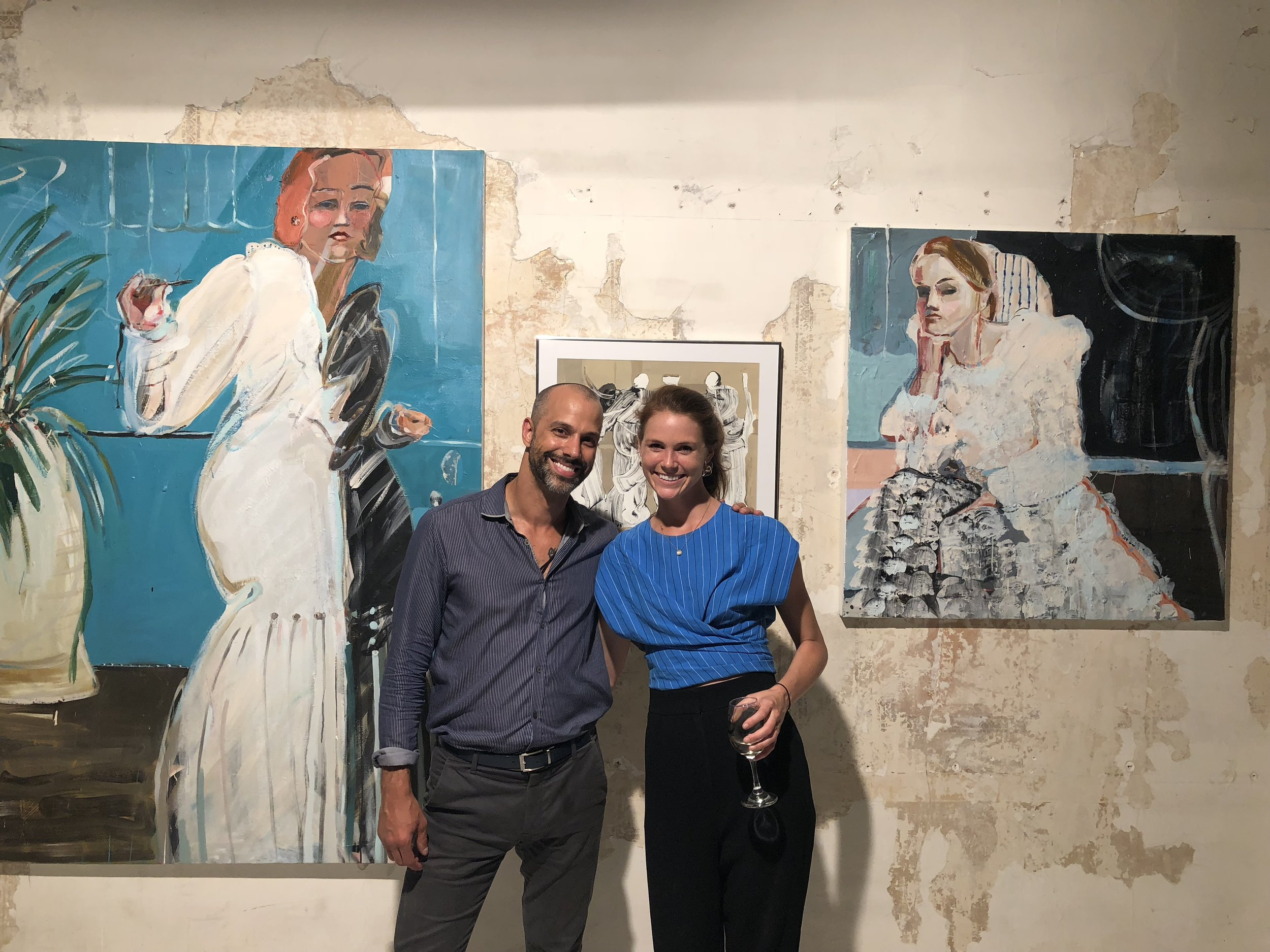 """Mary Ball with Ozymandias Wines' president and founder Rafe D'Amico, at """"Organized Chaos,"""" an Ozymandias Wines fundraiser in 2018. Mary's work is displayed on the wall behind them."""