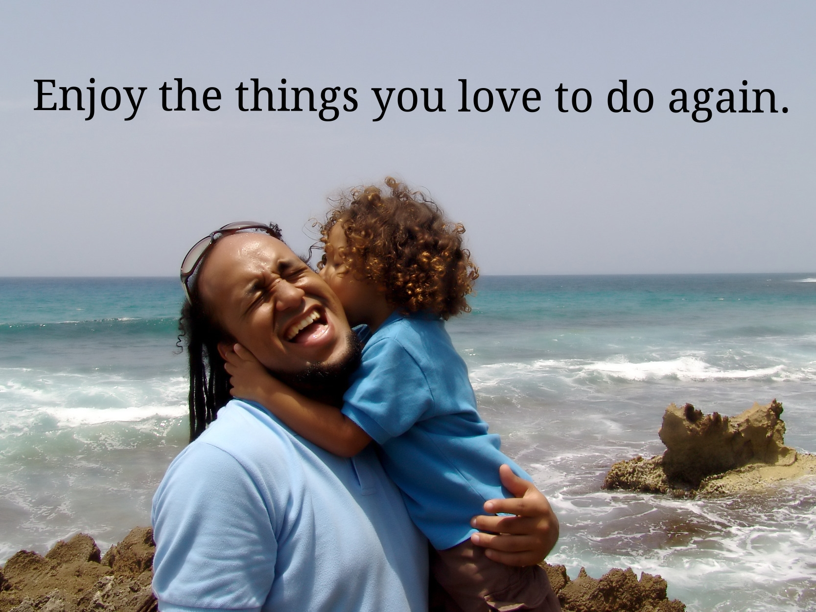Enjoy the things you love to do again (A dad holds his son on the beach).