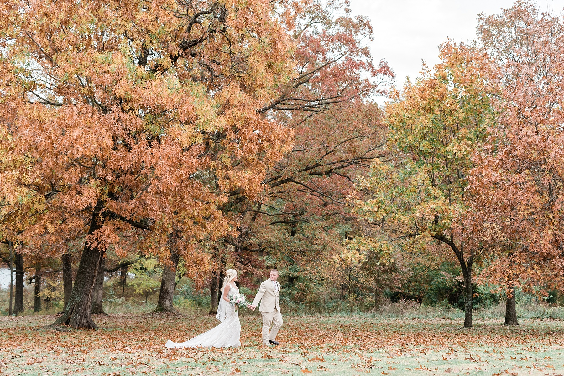 bride and groom as newlyweds walking in grove of trees at fall wedding at mighty oak lodge