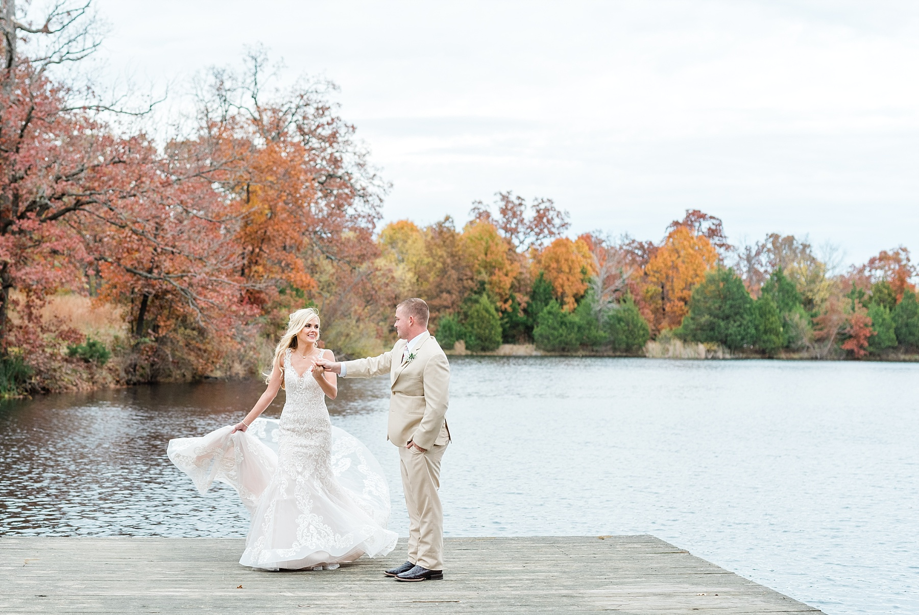 bride and groom dancing on dock by lake at lodge wedding in fall missouri