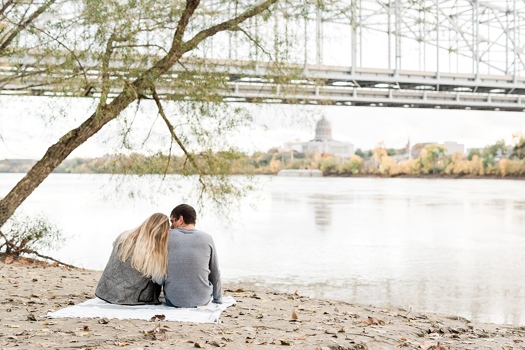 Couple Sitting On Shore Of Missouri River Jefferson City Missouri Watching Sun Set In Autumn