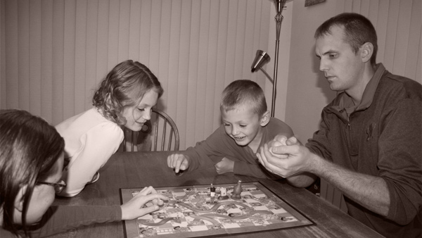 Creator Nikki and his three kids playing a modified version of Chutes & Ladders
