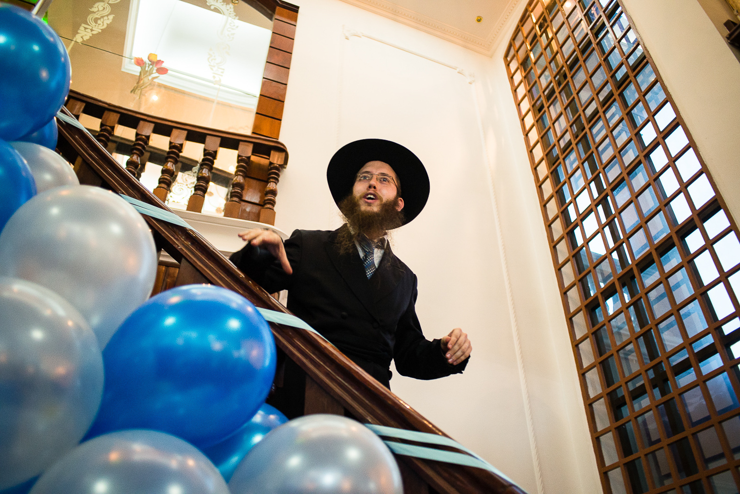 Rabbi Butman comes downstairs from the prayer room at the Chabad Center to invite all men upstairs to pray before the Bris (circumcision ceremony) of his newly born son.