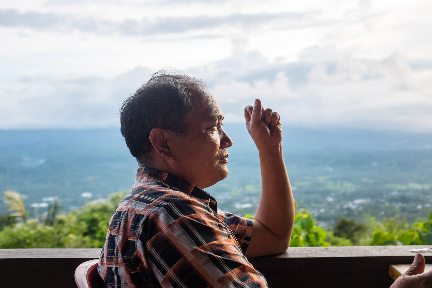 Ezra Sengkey, who came to be with his family and Vicky's after praying elsewhere, looks out over Sulawesi from the cafe next to a 62 meter high menorah, which was placed on one of Manado's highest mountains as a sign for the city's love of Israel.
