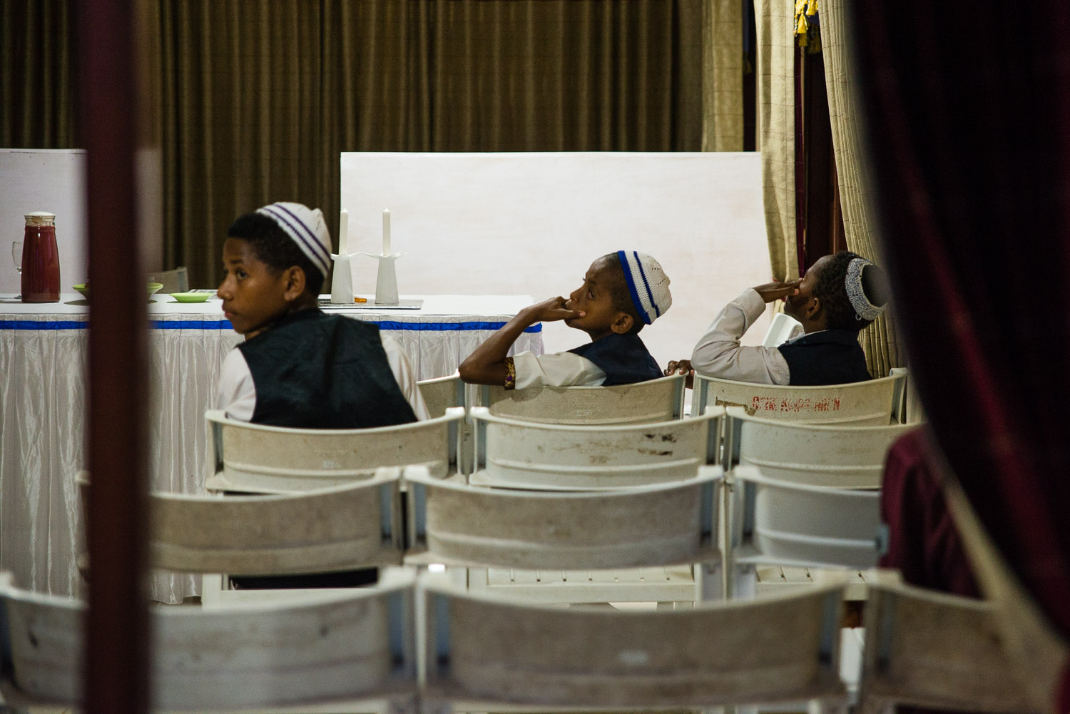 Annis, Charlie Kecil (little Charlie), and Hosea wait for Friday night Shabbat services to begin. The community wears their best clothes for Shabbat, including the children.
