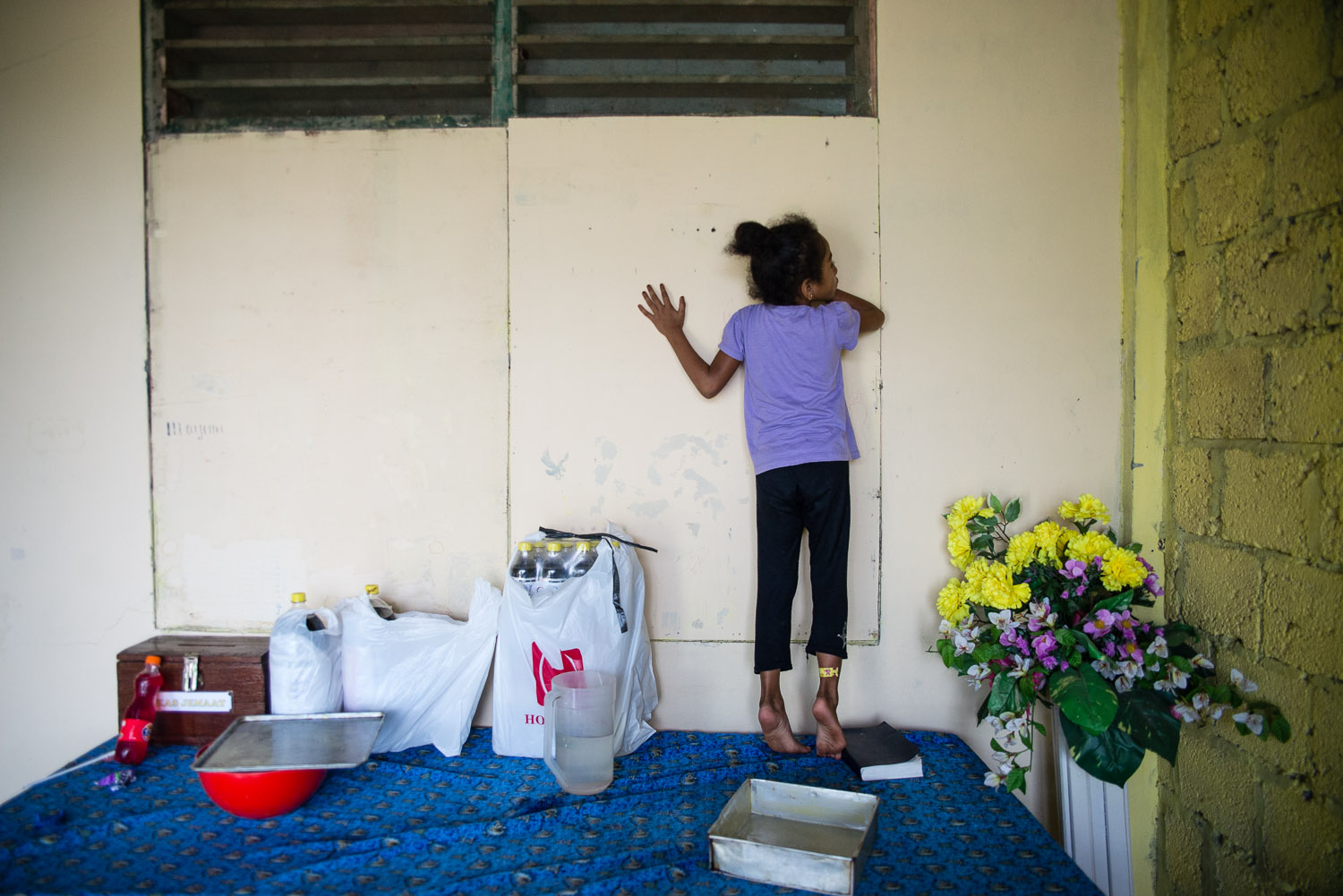 Shulamith, the youngest child of Diane and Harun, the leaders of the Papuan Jewish community, listens for her family's activities through the wall, standing on the table that Diane is to use to make Challah for the night's Shabbat dinner.