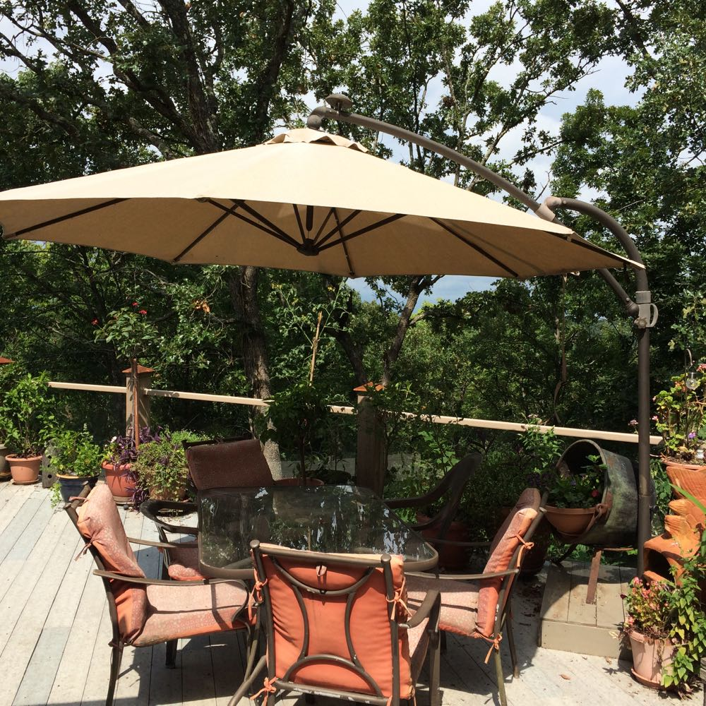 Deck umbrellas help break searing sun on potted deck plans at Bluebird Gardens.