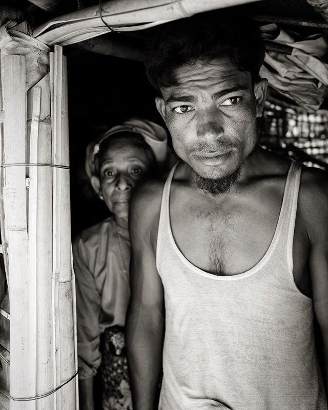 "Rohingya man and his mother. Living in a ""temporary"" makeshift shelter made of 60 pieces of bamboo and 5 tarps. 100+ MPH winds and torrential downpours begin in two weeks and there's a 70% likelihood that his ""home"" will be flattened during the storms."
