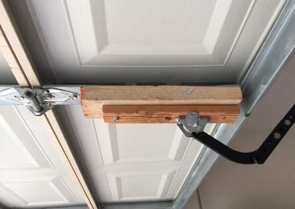 Wood attached to garage door pick up arm center stile