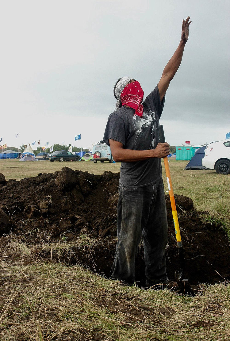 A Lakota man thanks The Creator for the water protectors win at Standing Rock, as he digs a hole to cook a turkey.