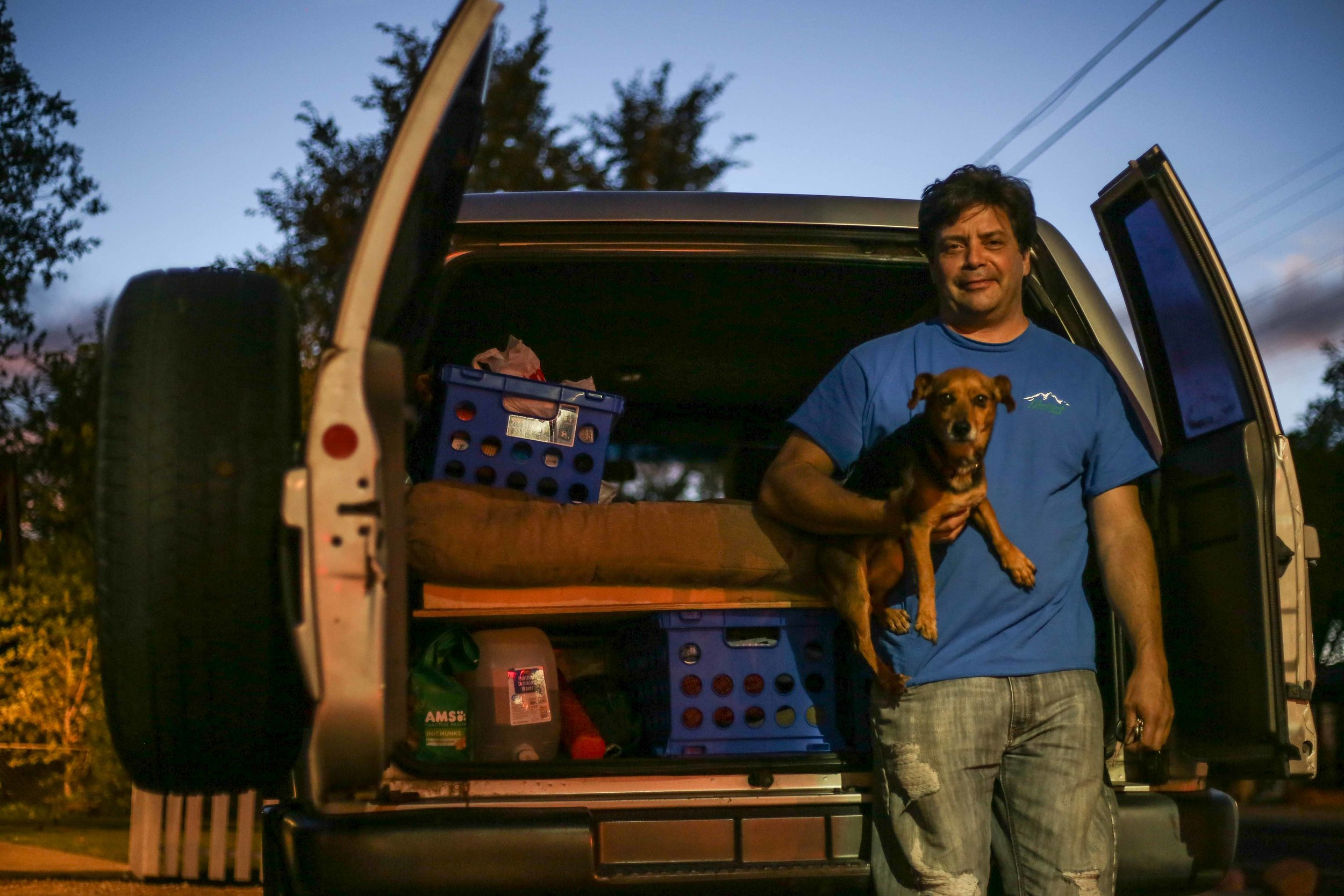 """Marty* and his dog Jax have been living in Reno for 14 years, but began living out of Marty's car this May. At Tesla, Marty checks batteries on a line, but he explains that his job could change any day. """"It just depends on how my superiors feel, one day I'm doing batteries, the next I'm driving the forklift, so who knows."""""""