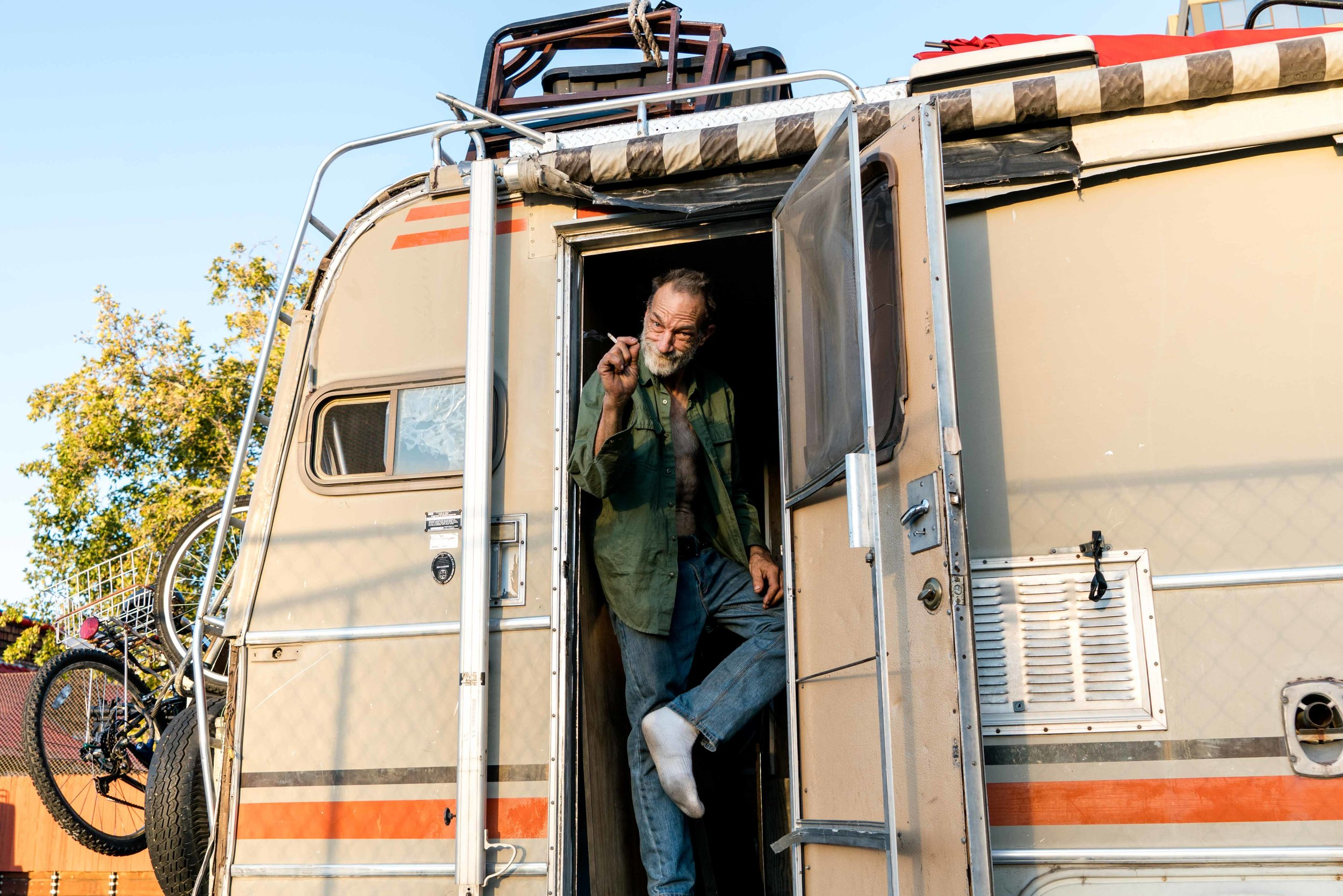 """""""I call her ugly,"""" B*. says as he motions to his 1980s home on wheels, which he got from a """"God-fearing-man"""" last December. B. is a street guitarist who recently left his job as a plumber at the Tesla factory. He says """"Ugly"""" is the best thing that ever happened to him because it allowed him to keep pursuing music in Reno."""