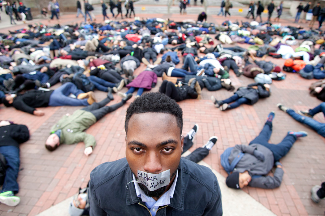 """The University of Michigan student William Royster, with the words """"Black Lives Matter"""" on tape over his mouth, at a demonstration in December in Ann Arbor, Mich.   Credit Patrick Record/The Ann Arbor News, via Associated Press"""