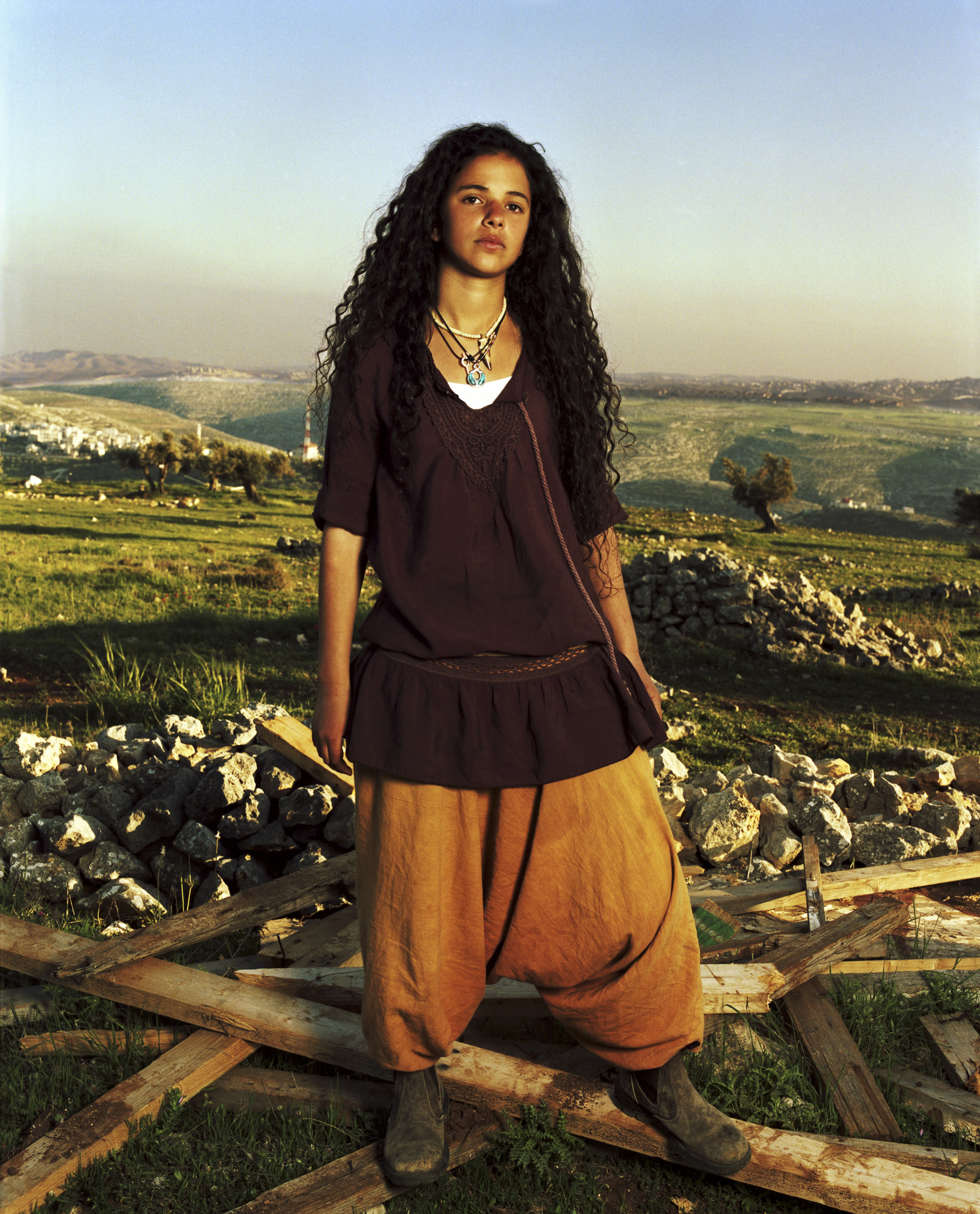 Bat El, 2011   Bat El lives alone on a hilltop outpost in the West Bank after being kicked out of Ben Zimra's school. She stands on the wood of her house the army just knocked down because it is considered illegal building.