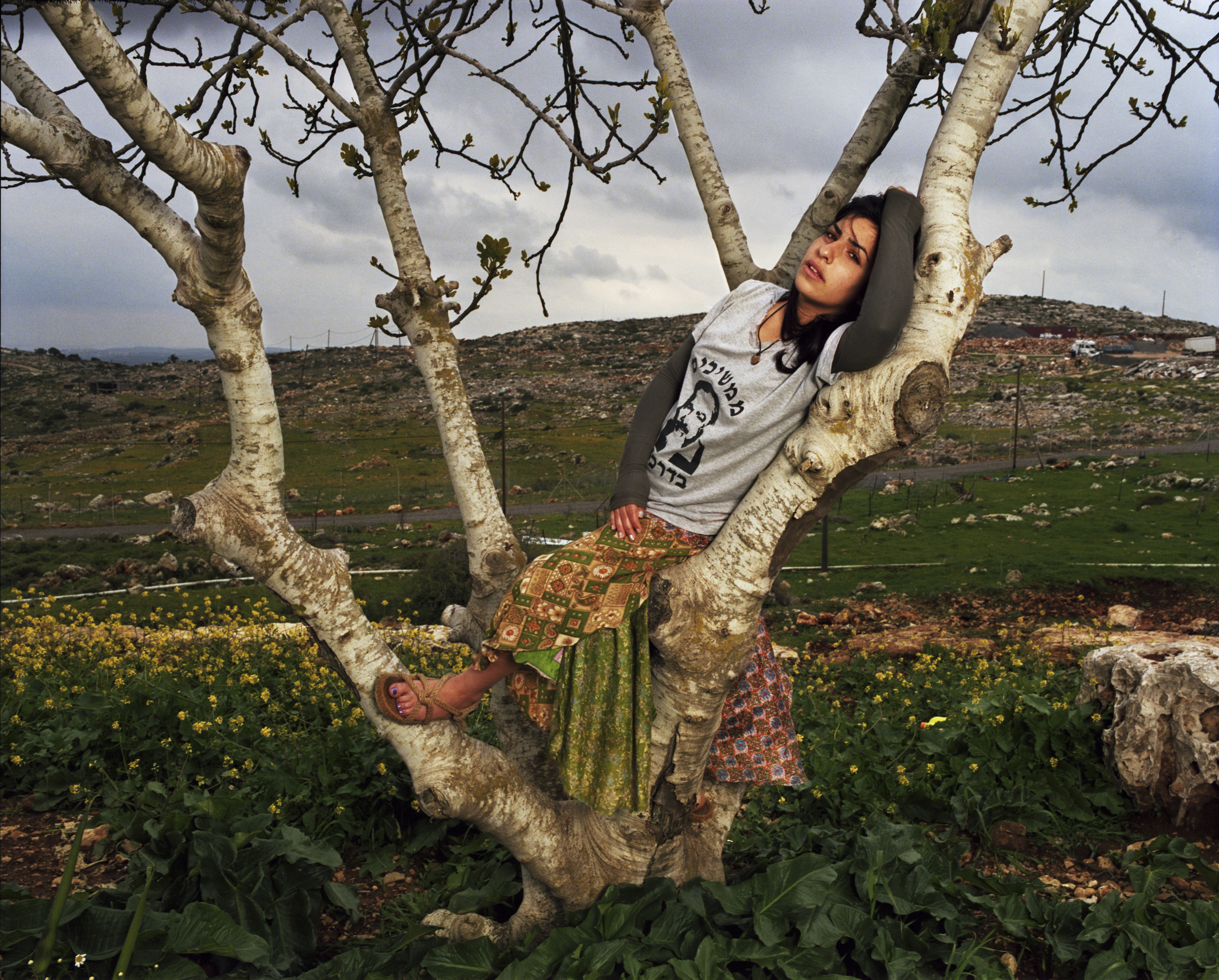 """Roni, 2011   Roni in her backyard of K'far Tapuach Settlement. The Itamar woman murdered in March was Roni's teacher. """"If someone comes to kill you, then you kill them first, says the Torah,"""" says Roni, who was wearing a Meir Kahane t-shirt."""