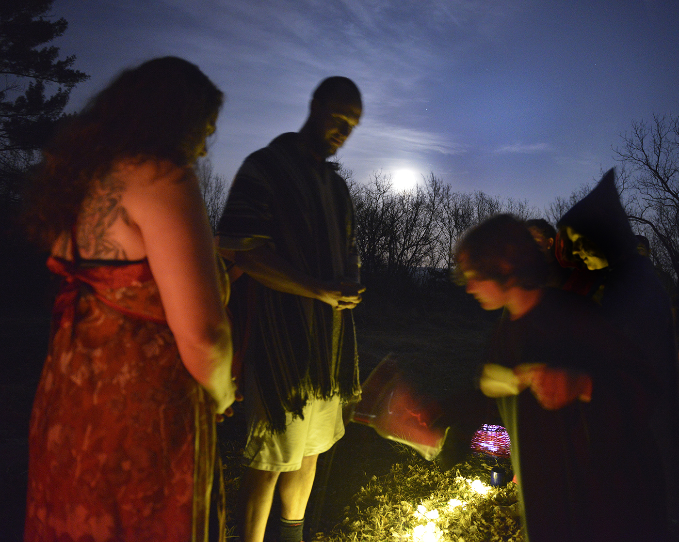 """Johanna Givens and Badger Johnson lead the children in ceremony to bless the garden outside of Oak Spirit Sanctuary during Imbolc. The children drank goat's milk mixed with honey and then offered it in a communion to the rest of the community with the phrase of, """"May you never thirst."""" Imbolic is a celebration of the early spring, when animals are beginning to prepare for offspring and produce milk. Milk, cream and butter is considered a treat because in past times they would not have had these through the winter months."""