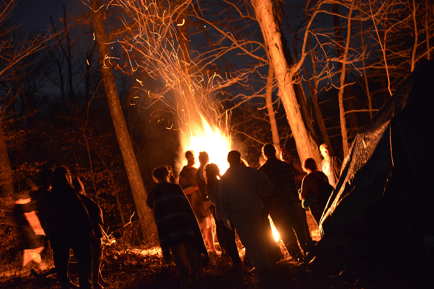 Members of the Wiccan community gather around the fire before participating in the reawakening plunge into Lake Gaia, named after the mother of life. They lit a fire to keep warm after going into the lake and sang songs to celebrate Imbolc. The plunge is a spiritual experience that represents rebirth into the spring.