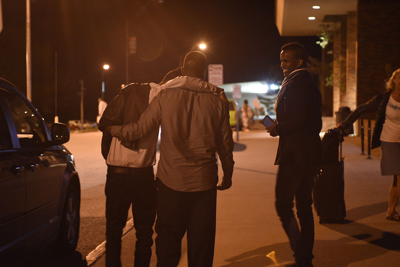 "Yasin Abdirahman and his father, Abshir Abdirahman, wrap their arms around each other as they walk with Yasin's older brother, Abdullahi Abdirahman, 17, to their car and begin to head home from the Columbia Regional Airport on Tuesday, April 18, 2017. Catholic Charities' refugee and immigration services helped reunite the family. ""We [were] going everyday [to] the refugee office, Catholic Charities, and telling them to help us. And they helped us really. And they were like us, worrying with us,"" said Barre."