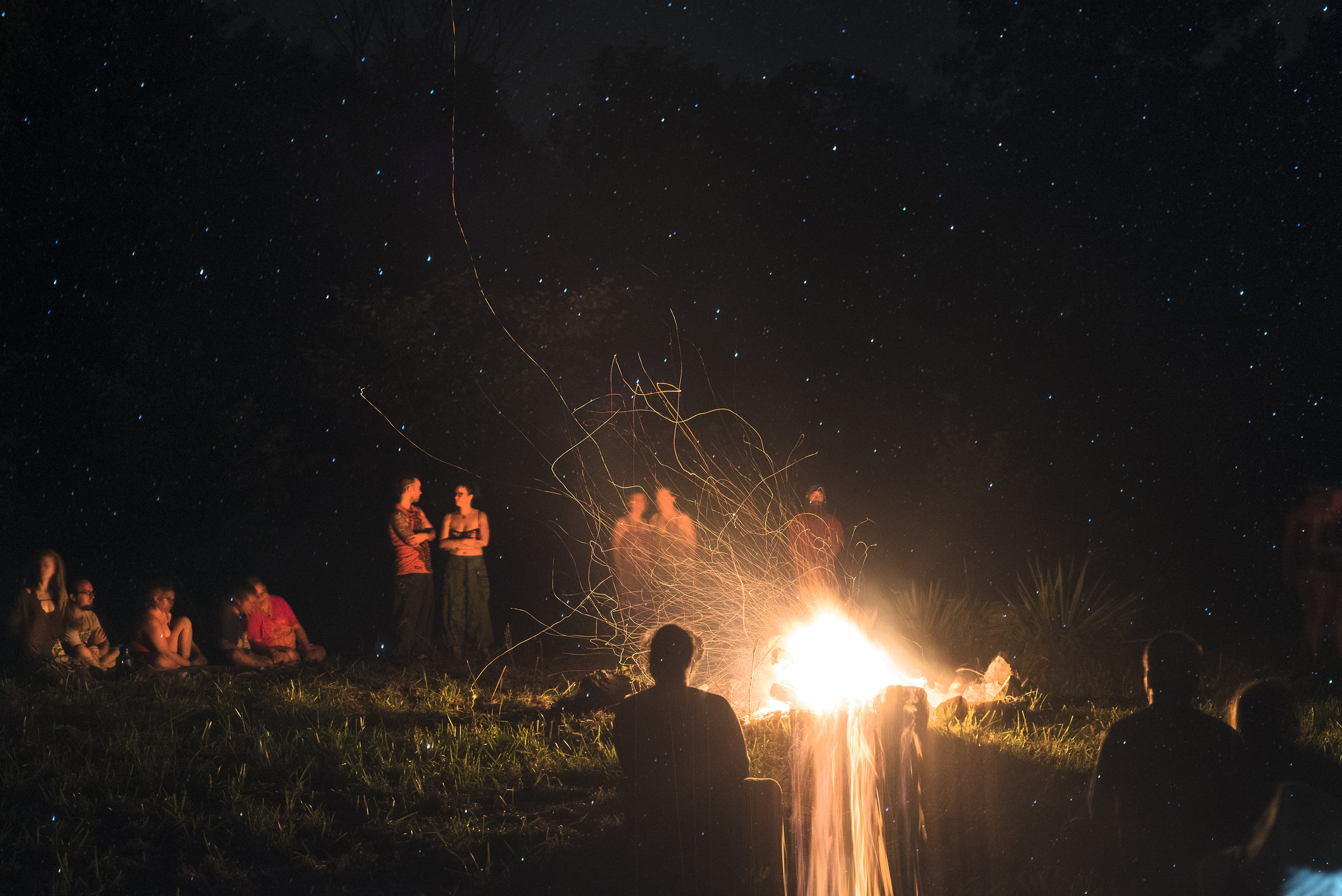 Pagans gather in a circle around a fire before a Thelemic ritual to the goddess of the sky, Nuit, at Oak Spirit Sanctuary on Sunday, August 21, 2017. The goddess calls on those who worship her for personal growth and expansion of consciousness. The pagans believe eclipses are times for working with their own gods and goddesses due to the heightened energies because a total solar eclipse is a rare astrological event to witness.  This photograph was taken with a long-exposure, allowing the night sky to be seen layered over the group surrounding the fire.