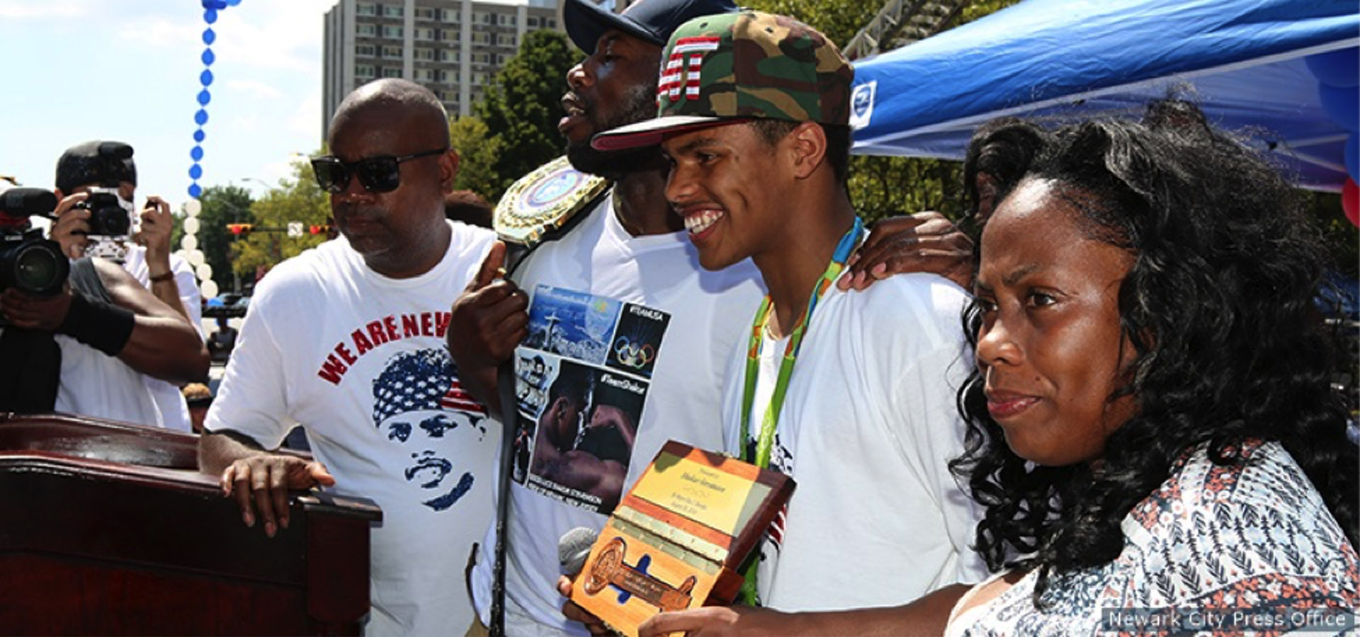 """Shakur Stevenson is joined at a parade in his honor by the Mayor of Newark, Ras Baraka (L); Stevenson's father, Shahid (2nd L); and mother, Malikah (R) on Aug. 28, 2016 in Newark, N.J.."" Photo by    Newark City Press Office   ."