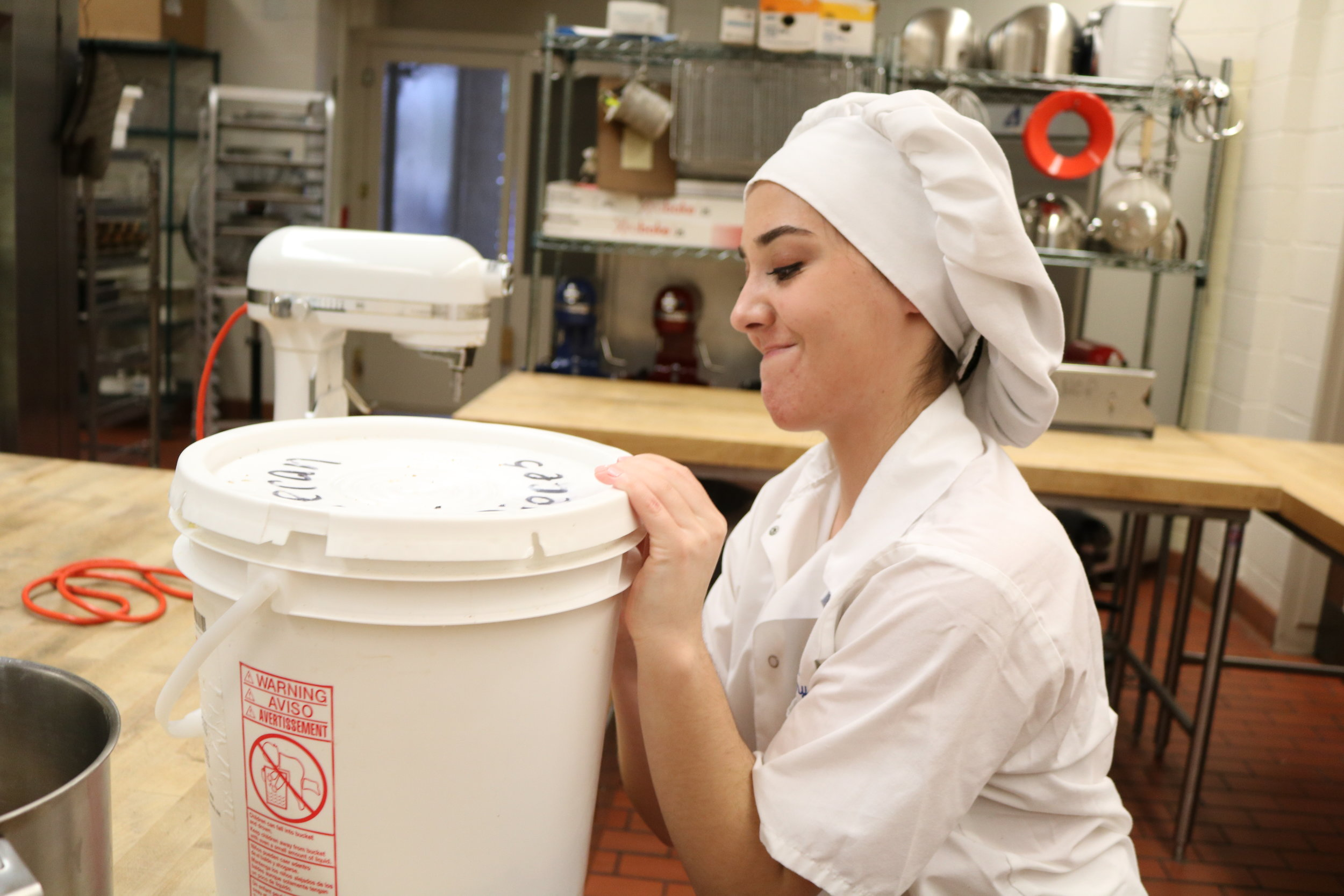 Ally Berrich, 17, works to open a tub of dough to bake for a commercial order in her baking and pastry course at the Center of Applied Technology North in Severn, Md., on May 5, 2016.