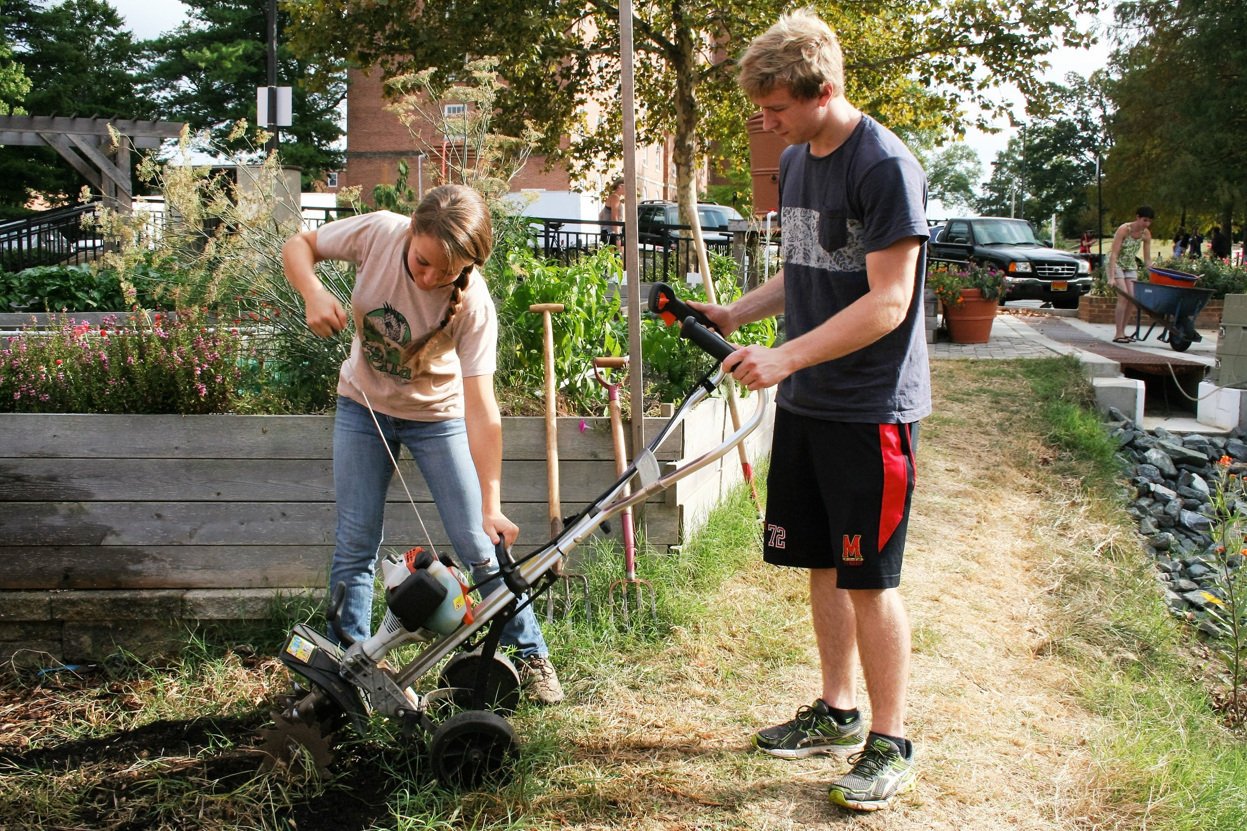 Meredith Epstein works with volunteer Philip Schwartz, a sophomore environmental and science technology major to start the engine of a plow to turn the fresh compost on Sept. 28, 2015.