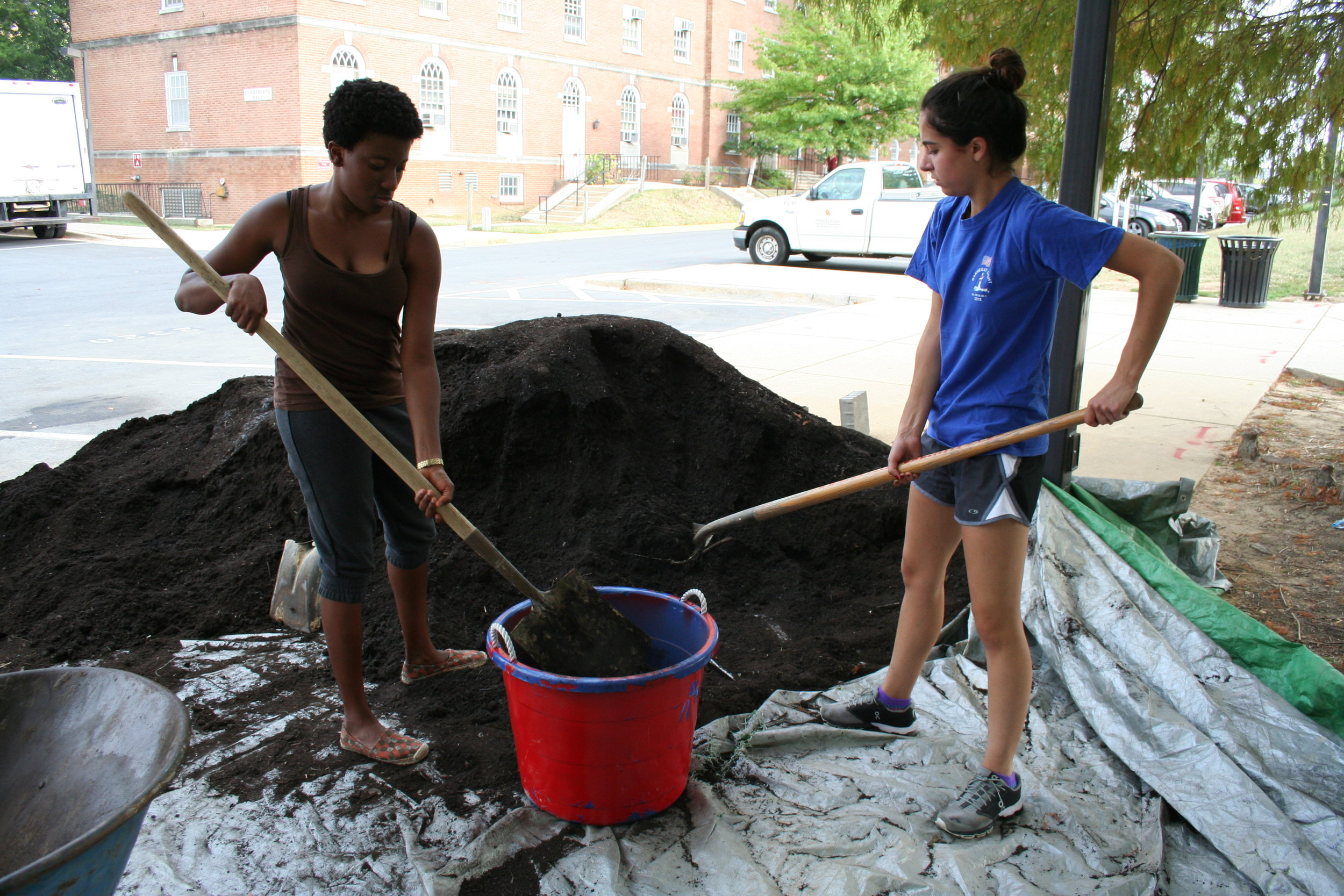 Asamaniwa Padi-Adjirackor, left, a sophomore agriculture and resource economics major and Claudia Romeo, right, a freshman elementary education major, begin their work hour at the Public Health Garden by shoveling and transporting compost provided by campus dining halls to the green space on Sept. 28, 2015. Transporting the entire heap to the garden was the goal of this work hour. Each club meeting has a different objective.