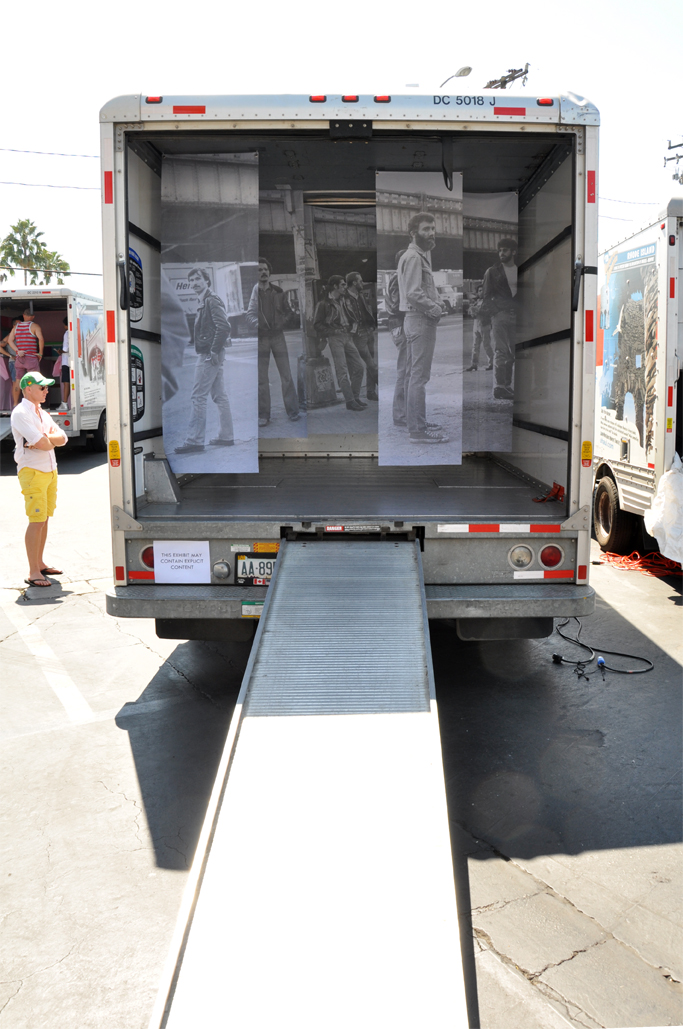 Exterior view of the installation. A viewer reads and essay by the artist,installed on the side of the truck, documenting the performative aspect of the piece's creation.