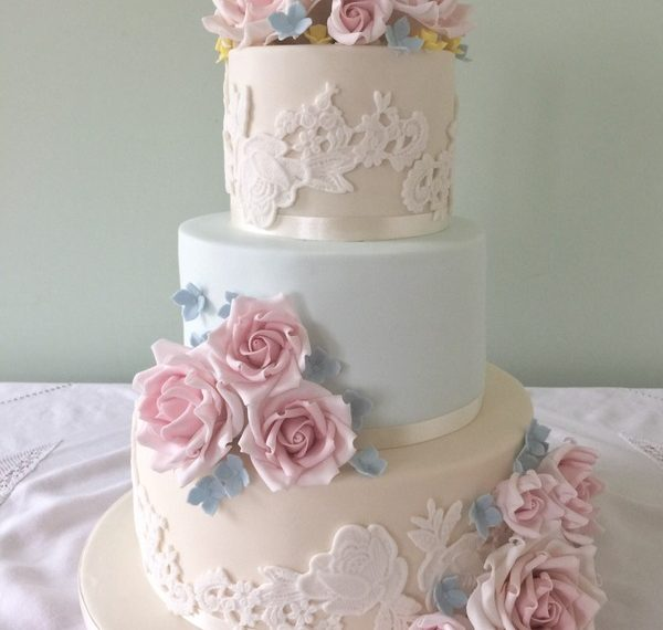 Fondant wedding cake dressed with sugar flowers by Sadie Smith