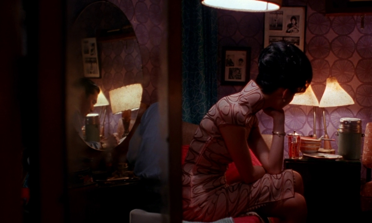 In the Mood for Love (2000):     Wong Kar Wai     Bringing an entirely different perspective to the melodrama film genre, Wong Kar Wai frames nearly each scene within corridors, windows and harsh shadows to signify the role of the observer verses the observed, relaying the pressuring and conflicting emotion without the characters even having to speak.
