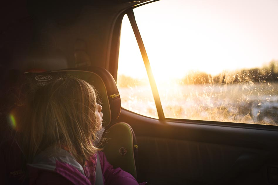 Girl looking out car window at gorgeous sunset.