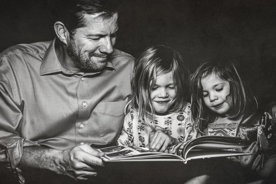FAther and two daughters smiling while looking at photo album.