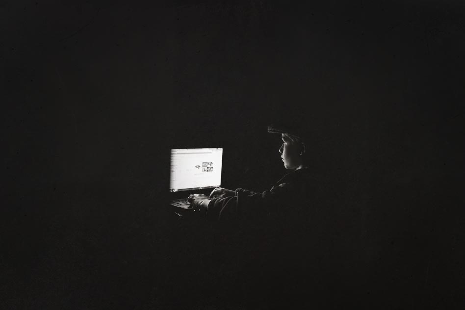 Black and white image of boy at computer
