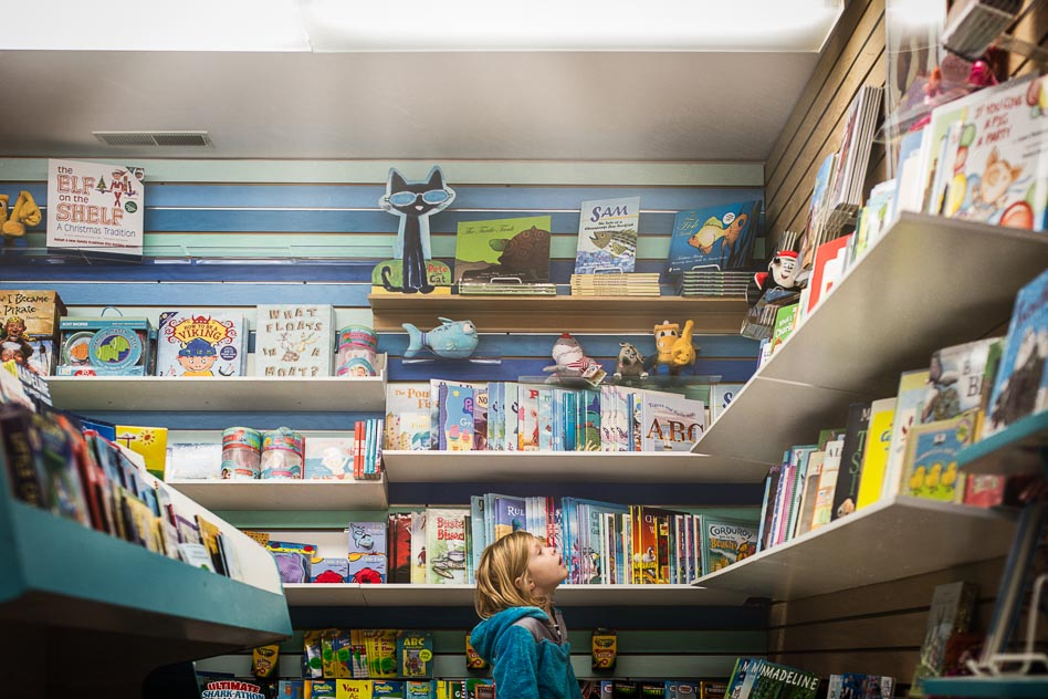 girl looking at books in colorful children's bookstore