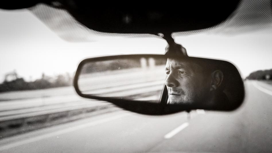 Mans face in rear view mirror in black and white photograph