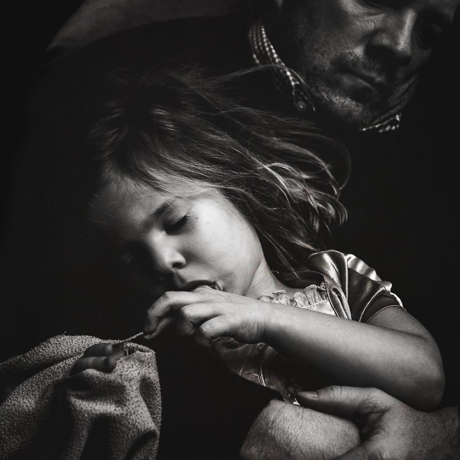 Black and white image of four year old girl asleep in her father's arms